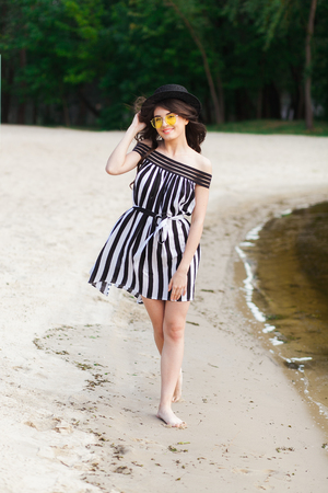 Luxury travel woman in black and white beachwear walking taking a stroll on sand summer beach. Girl tourist on summer holiday holding sun hat and yellow sunglasses at vacation resort