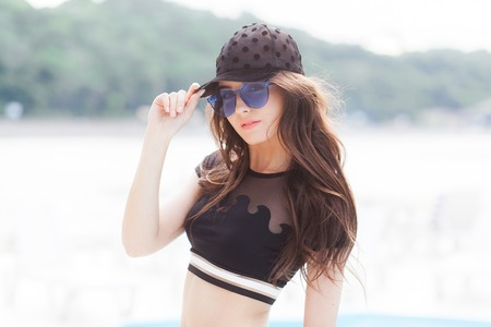 A young girl in a black cap, a black bathing suit and blue sunglasses stands on the beach background, looks at the camera