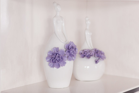 modern living room: Two vases in the form of a woman with flowers stand on a shelf Stock Photo
