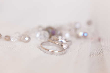 Wedding rings of white gold and angage ring on white background