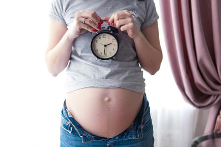 Schwangere Frau, die Wecker hält