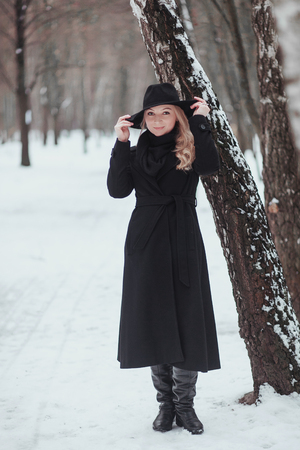 Woman winter snow nature portrait in black coat and hat