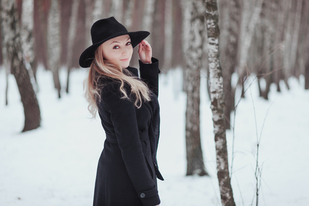 mistic: Woman winter snow nature portrait in black coat and hat