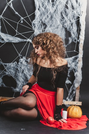Halloween witch girl sitting on the floor with black wall and spider web on background. Looking down