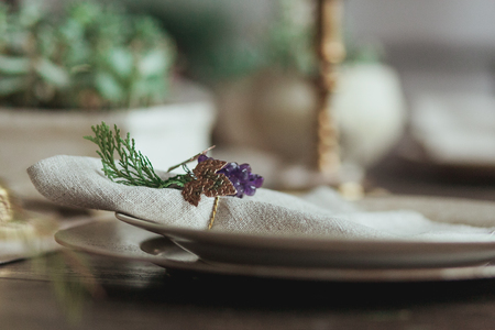 napkin ring: Decorated Christmas Dinner Table Setting of empty dish and sackcloth rustic napkin with decor ring in the form of grapes