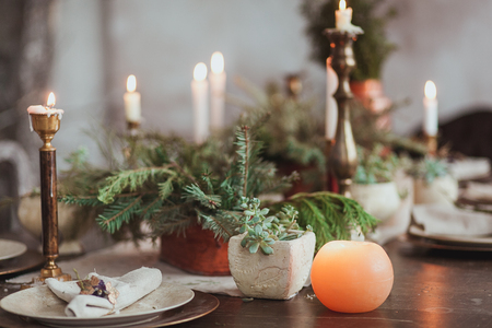 Weihnachtsfamilien-Abendtisch-Konzept. Kerzen, Weinlesegerichte, Tannenzweige mit klarem Kopienraum auf Wand