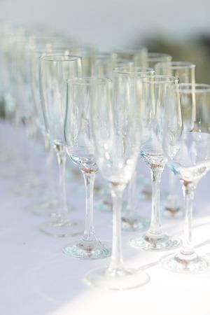 Lege champagneglazen op een rij op wit tafelkleed. Stockfoto