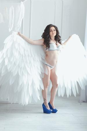 Mooi jong zwanger meisje met grote engelenvleugels in witte studio. Stockfoto