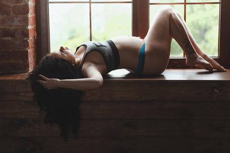 Pregnant woman lies on window sill in loft studio Stock Photo