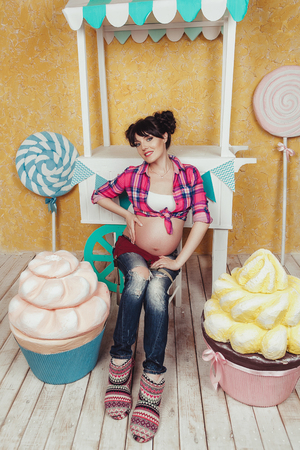 happy pregnant woman in toy candybar Stock Photo