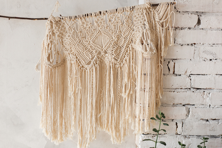 Loft interior white wall background, brick texture with knitted decor shawl