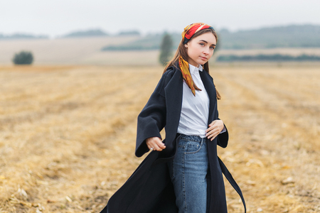 Portrait of a young brunette woman in black coat on a background of golden wheat field, autumn outdoors Stock Photo