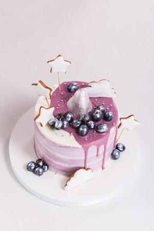 Trendy lilac round mousse cake with mirror glaze, pear, grapes and gingerbread decorated. isolated on gray background. Close-up view