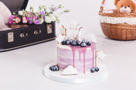 French mousse cake covered with lilac glaze on table. Purple modern European dessert with fruit decoration. Stock Photo