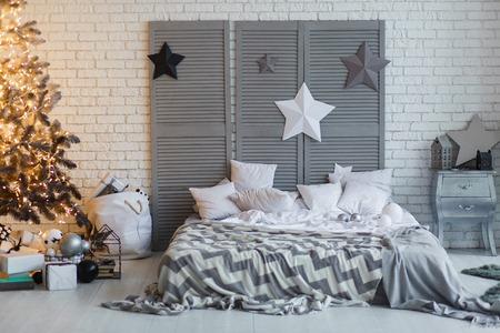 Das Schlafzimmer ist zu Weihnachten dekoriert. Gemütlicher grauer Hauptinnenraum. Neujahr Dekoration. helles Schlafzimmer mit großem Doppelbett. Weihnachtsbaum mit schüchterner Girlande.
