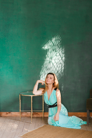Beautiful blonde woman in the interior studio sits on floor. Green empty wall on background. Copyspace