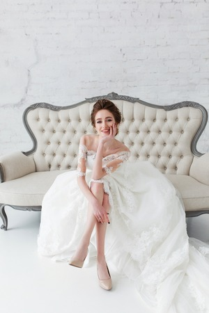 Beautiful, elegant bride sitting on vintage sofa in white nterior with brick wall background Stock Photo