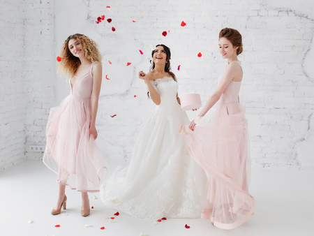 Bride and bridesmaids dancing in white studio with flying petals. Full-lenght portrait.