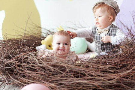 Little boy and girl sitting in natural nest with colorful Easter eggs. Home decoration - pastel color bunny banner