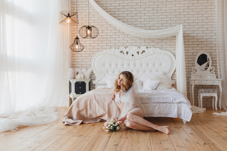 Beautiful bride in white lingerie sitting near bed in her bedroom with brick wall and looking to the window