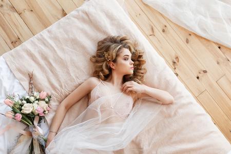 Bella giovane sposa in lingerie sexy si trova su un letto con un mazzo di fiori. Vista orizzontale superiore