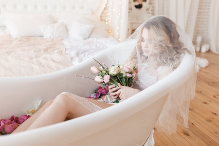 Beautiful bride in sexy lingerie lies in a bath with a bouquet of flowers covered with veil. Bedroom interior Stock fotó