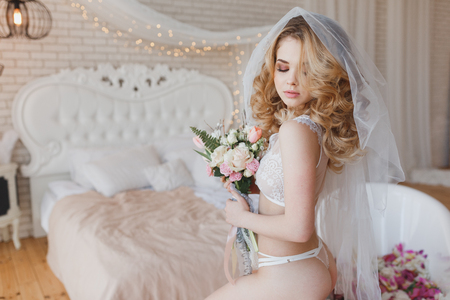 Sexy bride in lingerie showing her ass. Fashion portrait of model indoors. Beauty blonde woman with attractive body