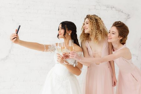Smiling young girls taking a selfie together. Bride and bridesmaid making morning photo