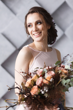 Smiling bride with bouquet close portrait in studio.