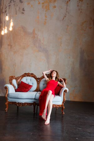 Beautiful girl in an amazing red dress on a background of minimal rustic loft wall sitting on white retro leather sofa