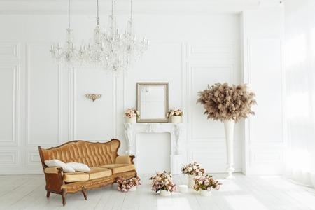 Beautiful classical white interior with a fireplace, brown sofa and a vintage chandelier. Retro, classics horizontal view.