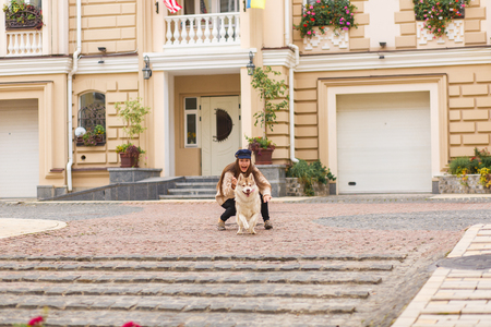 Girl is playing in the vintage Vozdvizhenka street with two dogs. City petsfriendly lifestyle Stock Photo