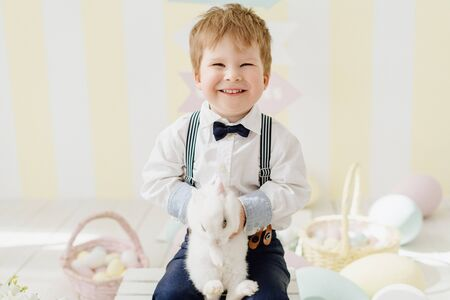 Smiling Little Boy Playing with Easter Rabbit Stock Photo - 126355849