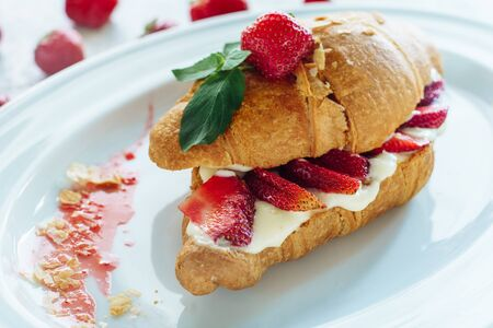 Sweet Croissant Cut Two with Cream and Strawberry Stock Photo
