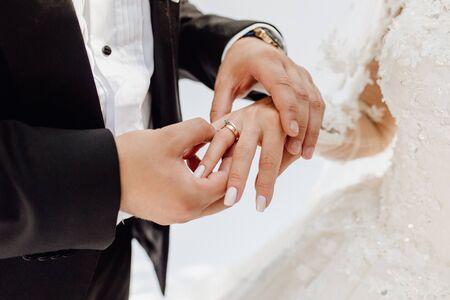 Novio poniendo joyas anillo de oro en el dedo de la novia