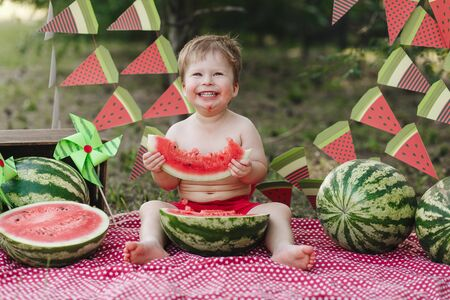 Happy child eating watermelon. Kid eat fruit outdoors. Little boy playing in the garden biting a slice of watermelon. Looking straight to camera Stock Photo