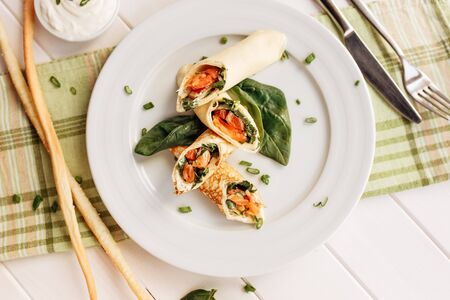 Rolls of thin pancakes with smoked salmon, horseradish cream cheese and spinach leaves. Side view with copy space