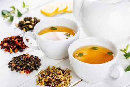 Verschillende soorten droge thee op witte houten achtergrond en twee kopjes en pot. Zijaanzicht versierd met munt en citroen Stockfoto