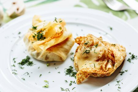Savory pancake like cake filled with mushrooms and ham on white plate with green dill