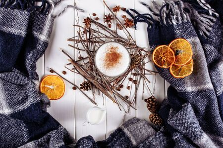 Glass cup of coffee latte on wooden table decorated with plaid, wood sticks and dried orange slices