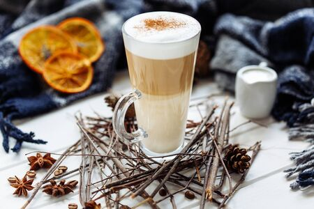 Glass cup of coffee latte on wooden table decorated with plaid, wood sticks and dried orange slices Stockfoto