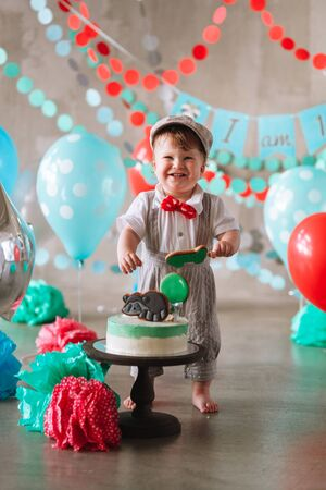 Adorable happy baby boy eating cake one at his first birthday cake smash party