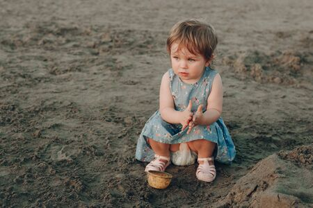 Little caucasian girl have fun digging in the sand at ocean beach, building sand castle. Stockfoto