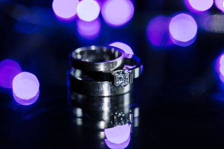 Classic white gold wedding and engagement rings close-up on wet sparkling background. Monochrome copy space photo 版權商用圖片