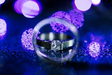 Close up diamond ring wedding ring inside circle. Creative wedding invitation card concept. Sparkling purple background with copy space.