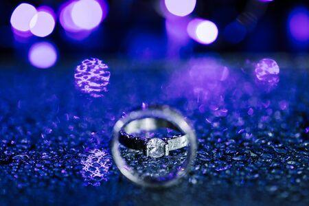 Close up anello di diamanti anello di nozze all'interno del cerchio. Concetto di carta di invito matrimonio creativo. Sfondo viola scintillante con spazio di copia. Archivio Fotografico