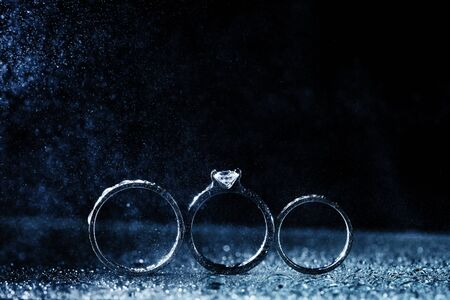 three wedding rings dark background with copy space. Shiny water drops like fog.