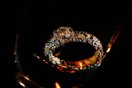 Wedding ring in champagne glass with golden bubbles. Close-up view on black background.