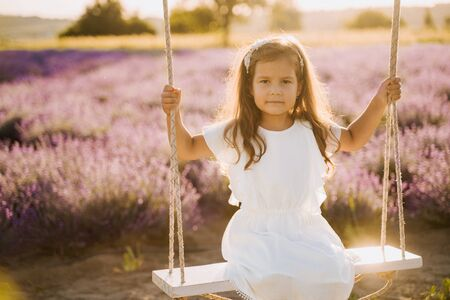 Beautiful Little Girl on Lavender Field Swinging