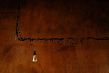 Light Bulb with Electric Cord on Rusty Metal Wall Background Copy Space. Industrial Pendant Lamp. Loft Vintage Grunge Style Interior and Edison Lightbulb. Classical Illumination Equipment 版權商用圖片